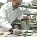 Smiling chef Karim Razgallah plating the cannelloni