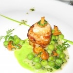Jumbo scallop wrapped in a thin slice of bacon on a bed of English peas and chanterelles