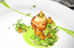 jumboscalloplaprime 300x196 Jumbo scallop wrapped in a thin slice of bacon on a bed of English peas and chanterelles
