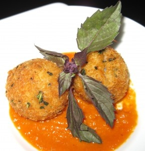 Risotto croquettes with a spicy tomato sauce and purple basil