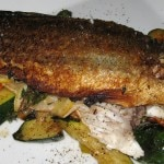 Grilled branzino flavored with slices of lemon, olive oil and thyme