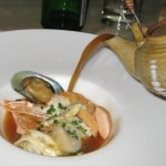 Seafod soup being poured to finish the bouillabaisse