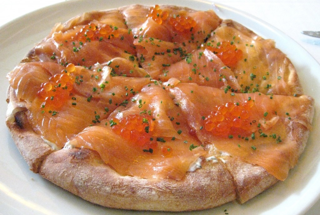 House smoked salmon pizza with shaved sweet onions, dill cream sauce, and salmon pearls