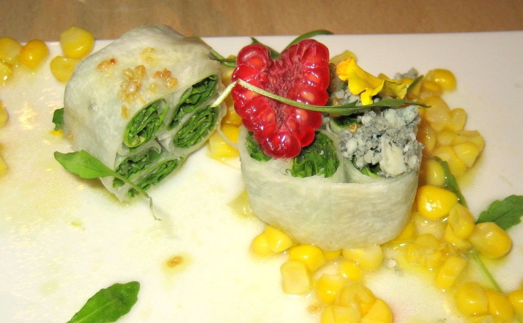 Organized arugula salad with raspberries, corn and Cabrales blue cheese