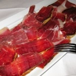 "Platter of pata negra cured ham, ""bellota bellota"" variety, with tomato on a slice of bread"
