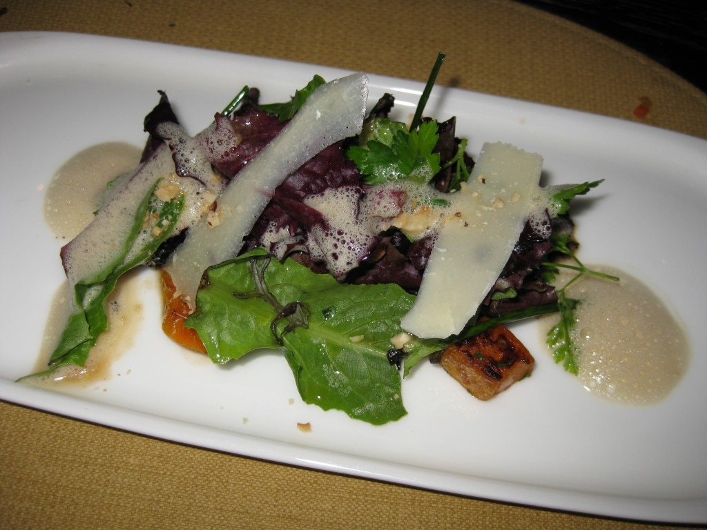 Green salad accompanied with black trumpet mushrooms and hazelnuts in a foie gras emulsion