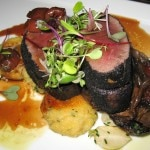 Ash-spiced venison loin with smoked polenta dumplings and dried cherry reduction