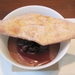 White sesame pot de crème with chocolate glaze, cherries and bugnes lyonnaise pastry