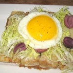 Caramelized onion and frisee tart with olives, gruyere and fried egg