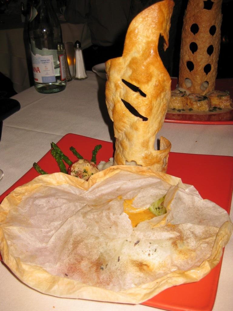 Branzino al Cartoccio: Chilean sea bass baked in a parchment basket, presented in a Spanish saffron and seafood infusion