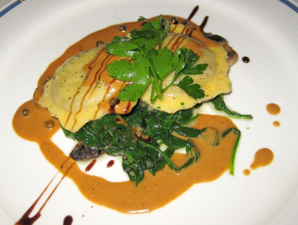 Portobello Mushroom Ravioli: Portobello mushroom stuffed ravioli seved with glace and green peppercorns over sautéed locally grown spinach