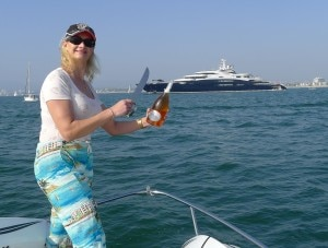 Sophie Gayot sabraging a bottle of Champagne on the bow of Serene, Yury Scheffler's yacht