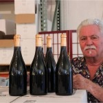 Bruce Perry signing bottles from his Papapietro Perry Winery