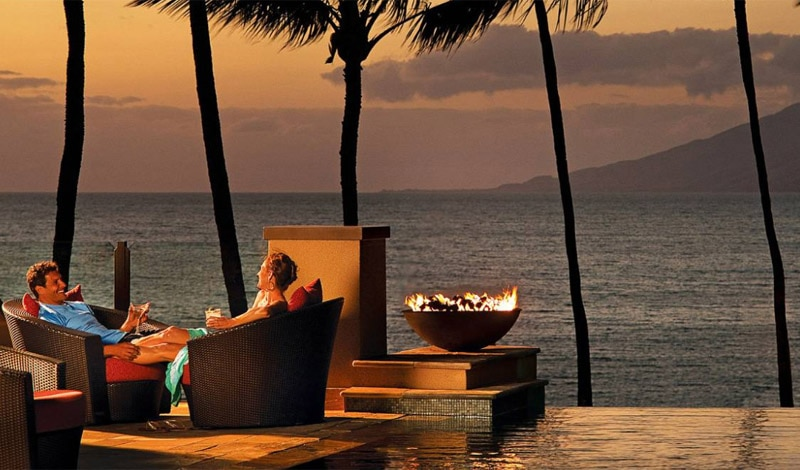 A couple relaxes by the pool at Four Seasons Resort Maui at Wailea