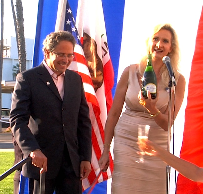 Sophie Gayot sabraging a bottle of Besserat de Bellefon Brut NV Champagne with Santa Monica mayor Richard Bloom