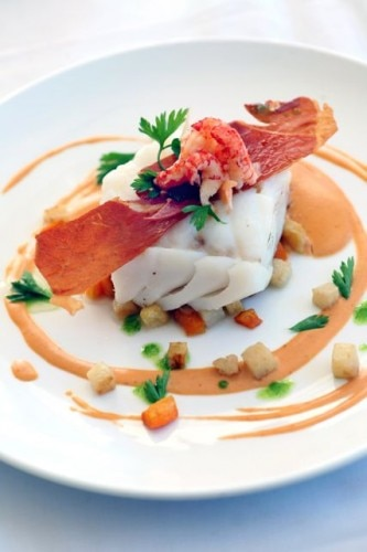 Fresh, arctic cod from Senja served with semi-dried ham, lobster sauce, garlic roasted root vegetables, crayfish and salt baked potatoes