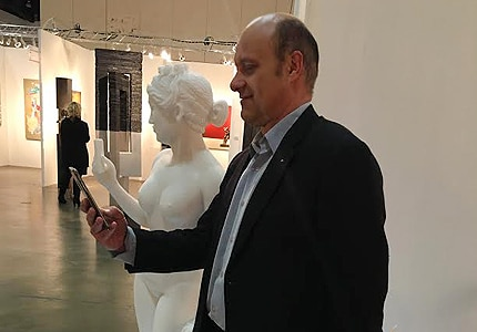 "Alain Gayot having fun with Matthew LaPenta's ""Immortalization of Self"" marble statue at the LA Art Show"