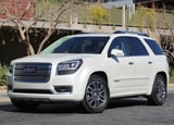 A three-quarter front view of a white 2013 GMC Acadia Denali