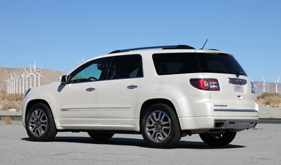 A three-quarter rear view of a 2013 GMC Acadia Denali
