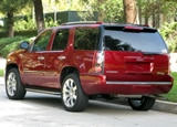 A three-quarter rear view of a red 2009 GMC Yukon Denali Hybrid
