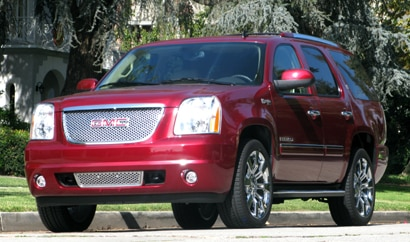 A three-quarter front view of a red 2009 GMC Yukon Denali Hybrid
