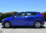 A side view of a blue 2012 Hyundai Accent 5-door hatchback