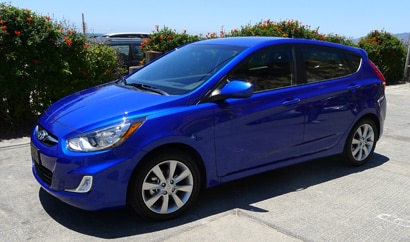 A three-quarter front view of a blue 2012 Hyundai Accent