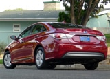 A three-quarter rear view of a red 2012 Hyundai Sonata Hybrid