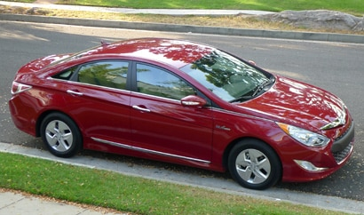 A side view of a red 2012 Hyundai Sonata Hybrid