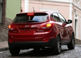 A three-quarter rear view of a red 2010 Hyundai Tucson