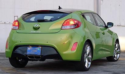 A three-quarter rear view of a green 2012 Hyundai Veloster
