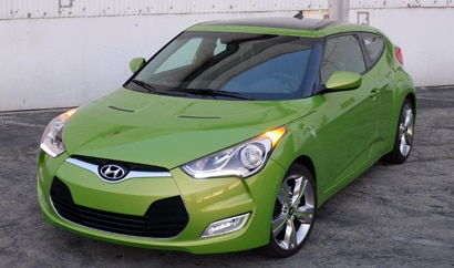 A three-quarter front view of a green 2012 Hyundai Veloster