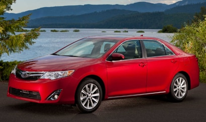 A three-quarter front view of a red 2012 Toyota Camry