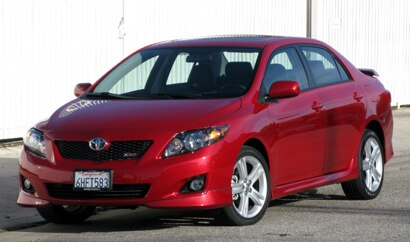 A three-quarter front view of a red 2010 Toyota Corolla