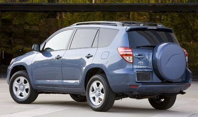 A three-quarter rear view of a blue 2011 Toyota RAV4