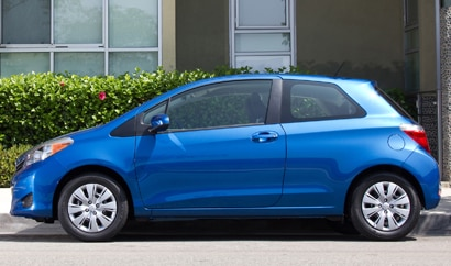A side view of a blue 2012 Toyota Yaris 3-Door Liftback