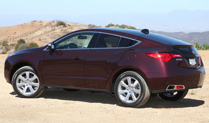 A three-quarter rear view of a dark cherry pearl 2010 Acura ZDX on a mountain road