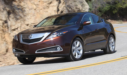 A three-quarter front view of a dark cherry pearl 2010 Acura ZDX on a mountain road