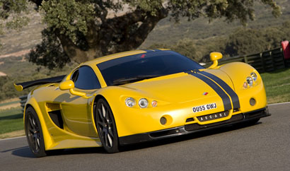A three-quarter front view of a yellow Ascari A10 on the road