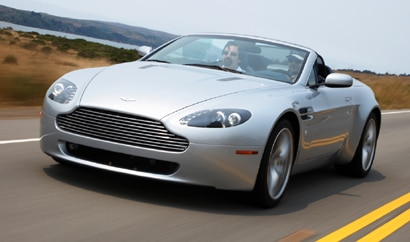A three-quarter front view of a silver 2009 Aston Martin V8 Vantage Roadster cruising on the open road