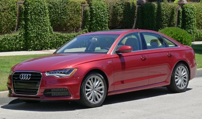 A three-quarter front view of a red 2012 Audi A6 Quattro