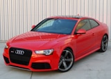 A three-quarter front view of a red 2013 Audi RS 5 Coupe