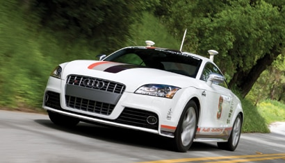 A three-quarter front view of the Pikes Peak Autonomous Audi TTS on the road