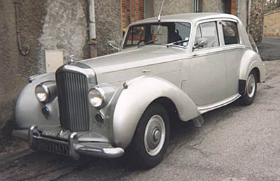 A three-quarter front view of a gray 1954 Bentley R-Type