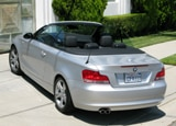 A three-quarter rear view of a silver 2008 BMW 128i Convertible