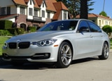 A three-quarter front view of a silver 2012 BMW 328i
