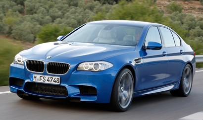 A three-quarter front view of a blue BMW M5 in action
