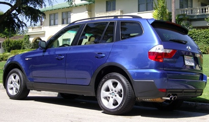 A three-quarter rear view of a blue 2007 BMW X3 3.0si