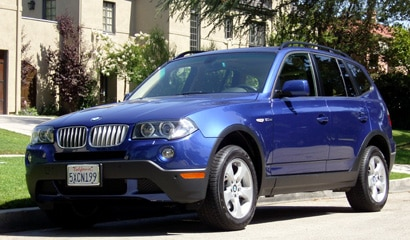 A three-quarter front view of a blue 2007 BMW X3 3.0si