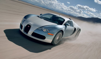 A view of a gray and blue 2006 Bugatti Veyron 16.4 racing across a dry lake bed